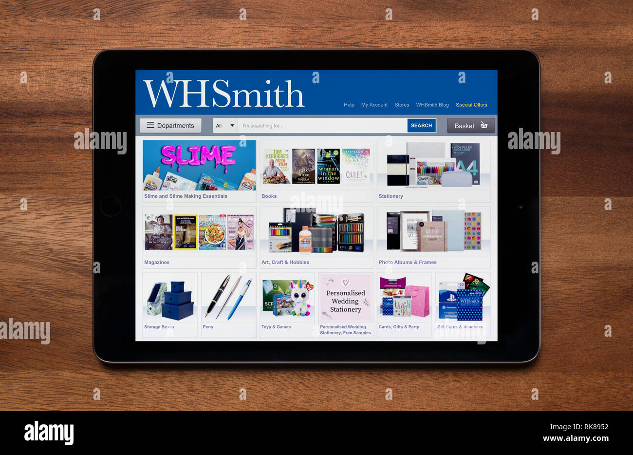 The website of WH Smith is seen on an iPad tablet, which is resting on a wooden table (Editorial use only). - Stock Image