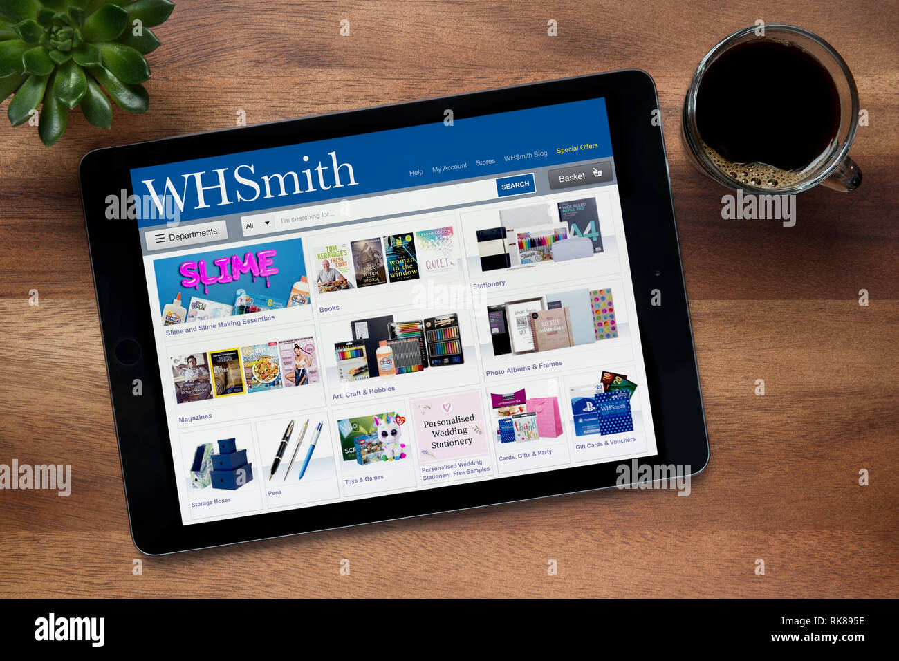 The website of WH Smith is seen on an iPad tablet, on a wooden table along with an espresso coffee and a house plant (Editorial use only). - Stock Image