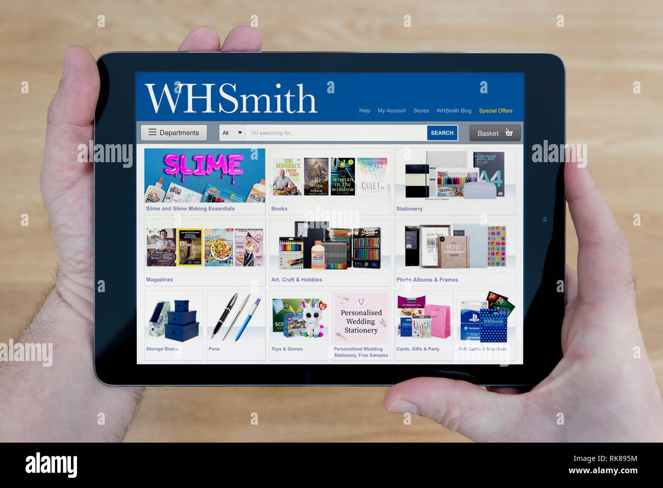 A man looks at the WH Smith website on his iPad tablet device, shot against a wooden table top background (Editorial use only). - Stock Image