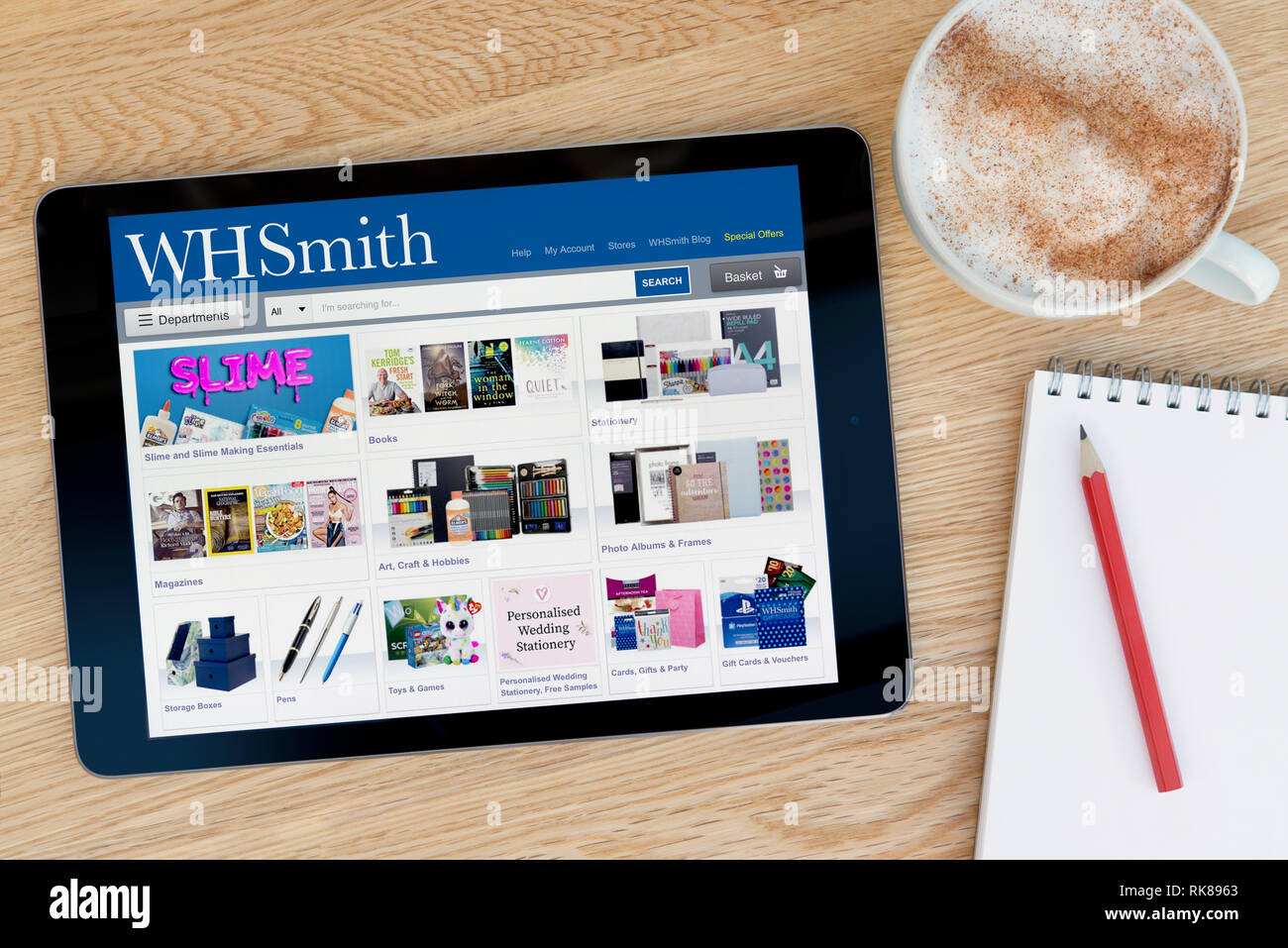 The WH Smith website features on an iPad tablet device which rests on a wooden table beside a notepad (Editorial use only). - Stock Image
