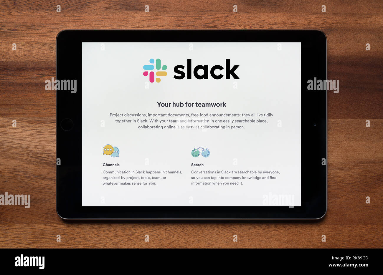 The website of Slack is seen on an iPad tablet, which is resting on a wooden table (Editorial use only). - Stock Image