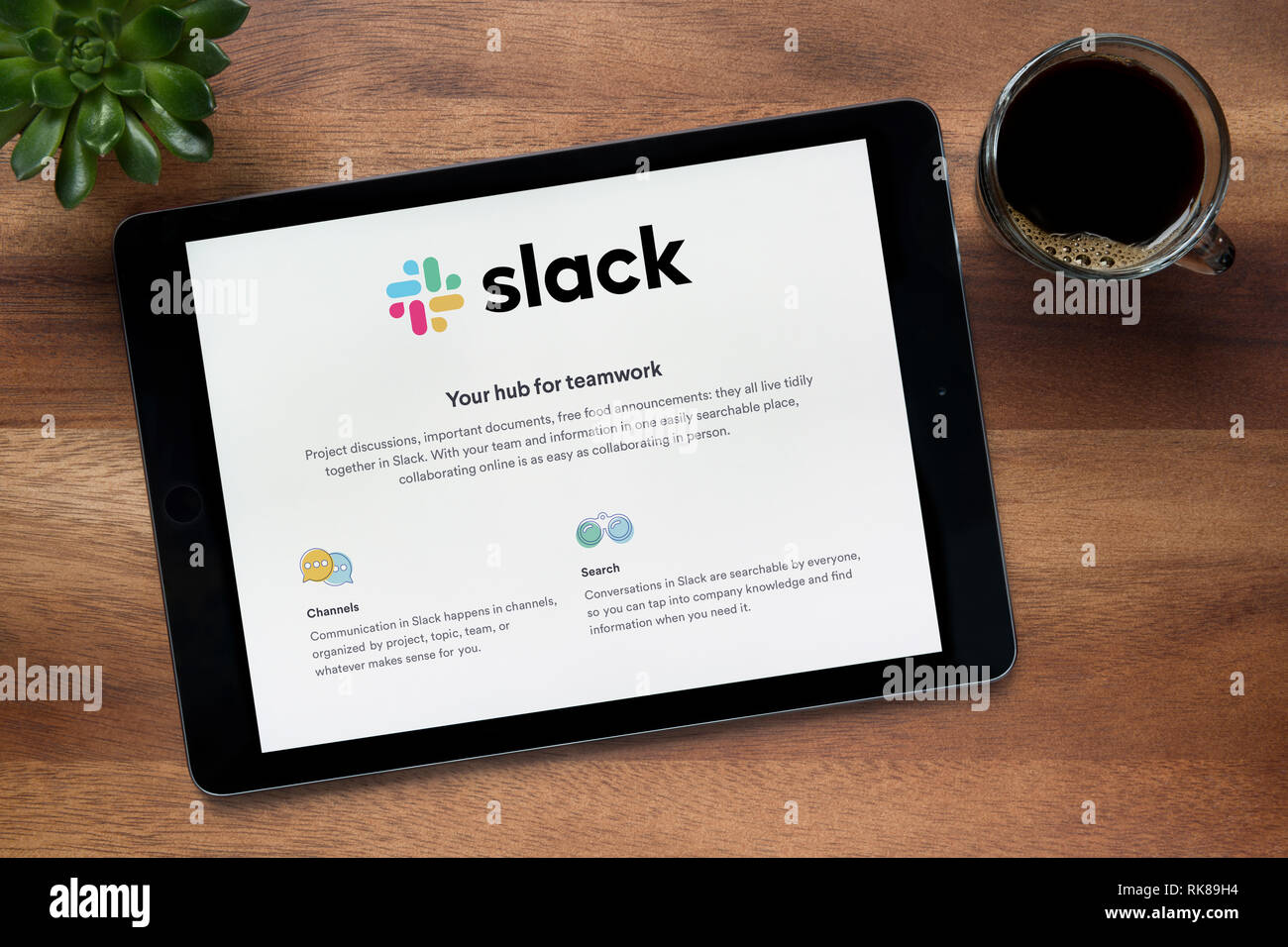 The website of Slack is seen on an iPad tablet, on a wooden table along with an espresso coffee and a house plant (Editorial use only). - Stock Image