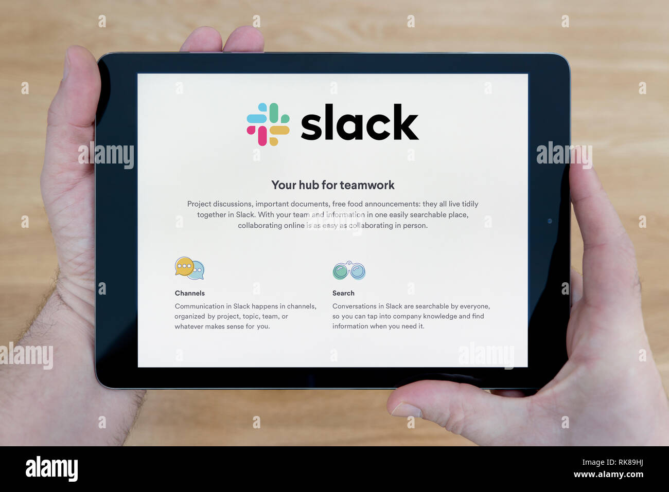 A man looks at the Slack website on his iPad tablet device, shot against a wooden table top background (Editorial use only). - Stock Image