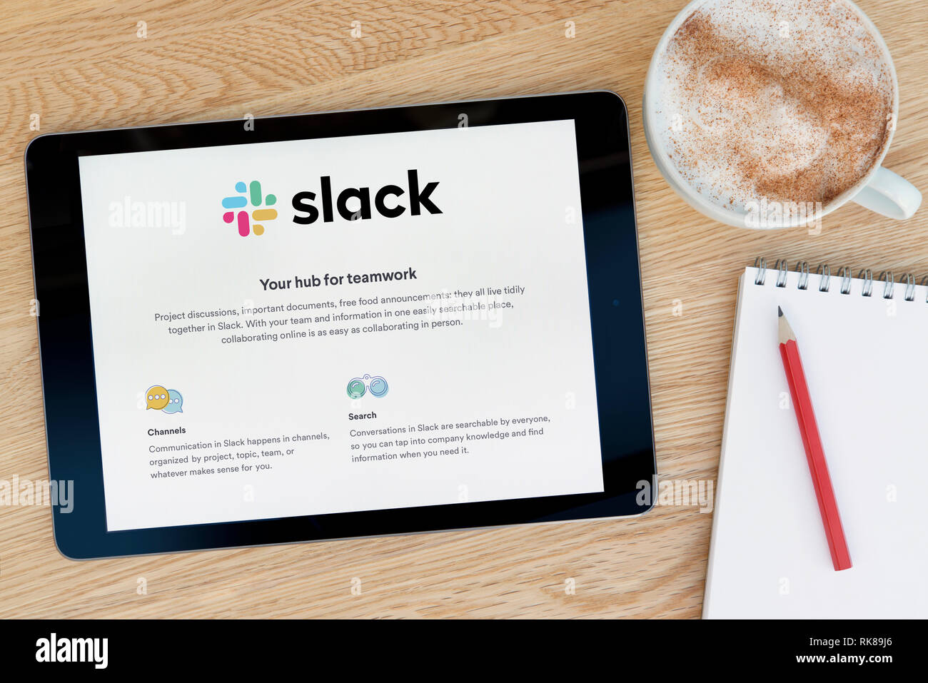 The Slack website features on an iPad tablet device which rests on a wooden table beside a notepad (Editorial use only). - Stock Image