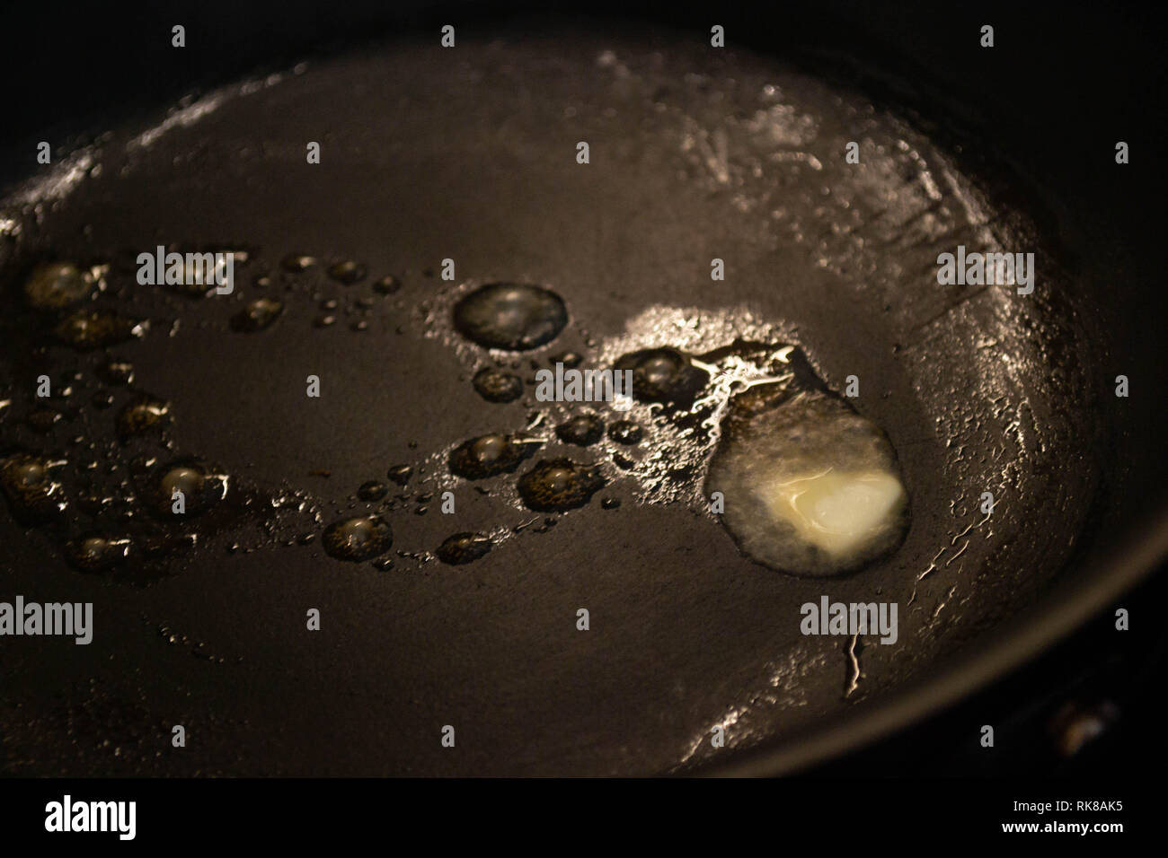 Melted butter sizzling in a nonstick teflon pan - Stock Image