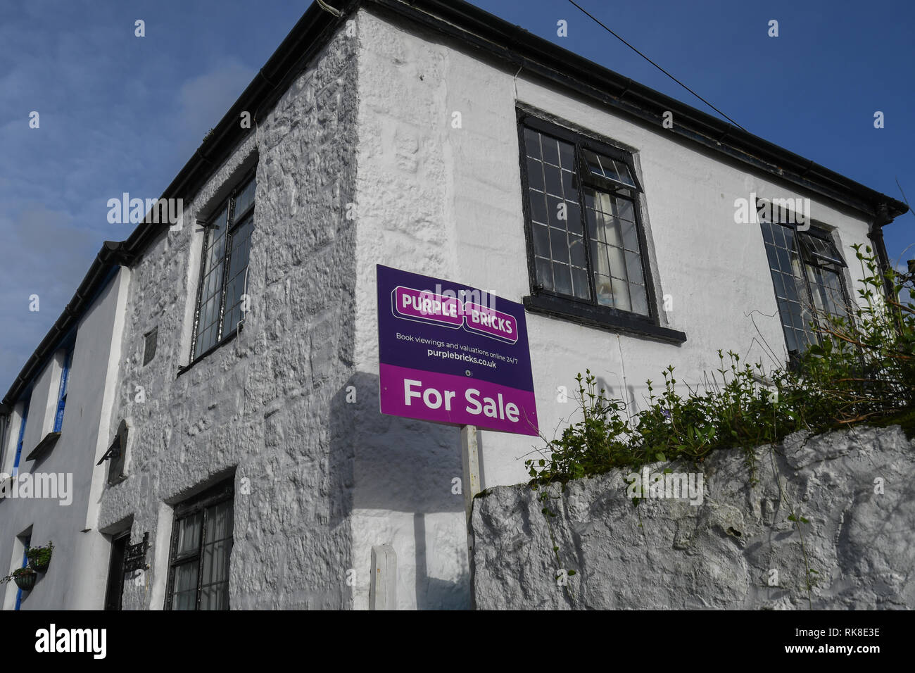Purple bricks estate agency sign outside a building - Stock Image