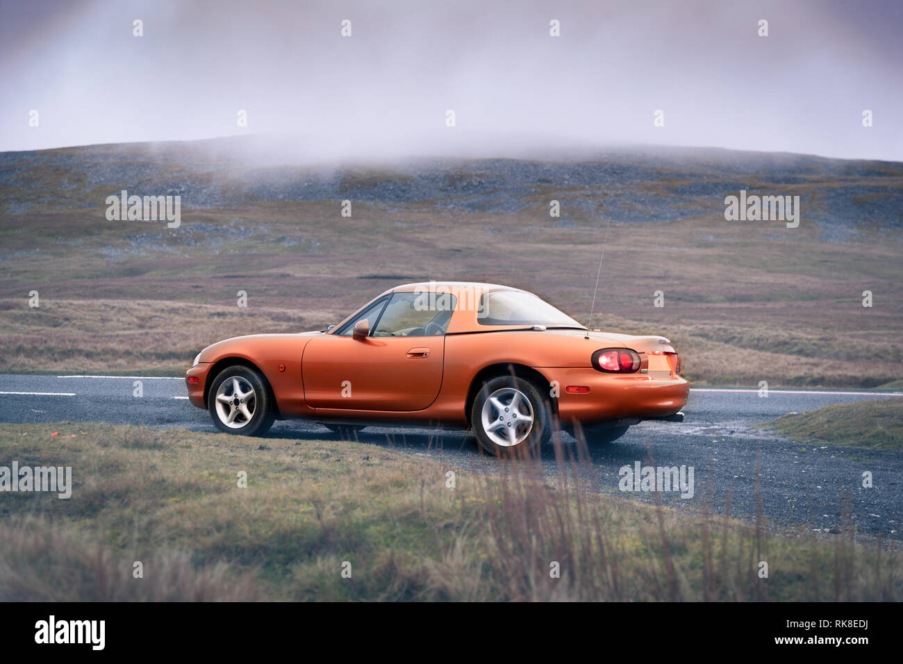 Sporty little gold coupe with hard top parked on the road.  Up a Welsh mountain on a grey english day in the clouds. - Stock Image