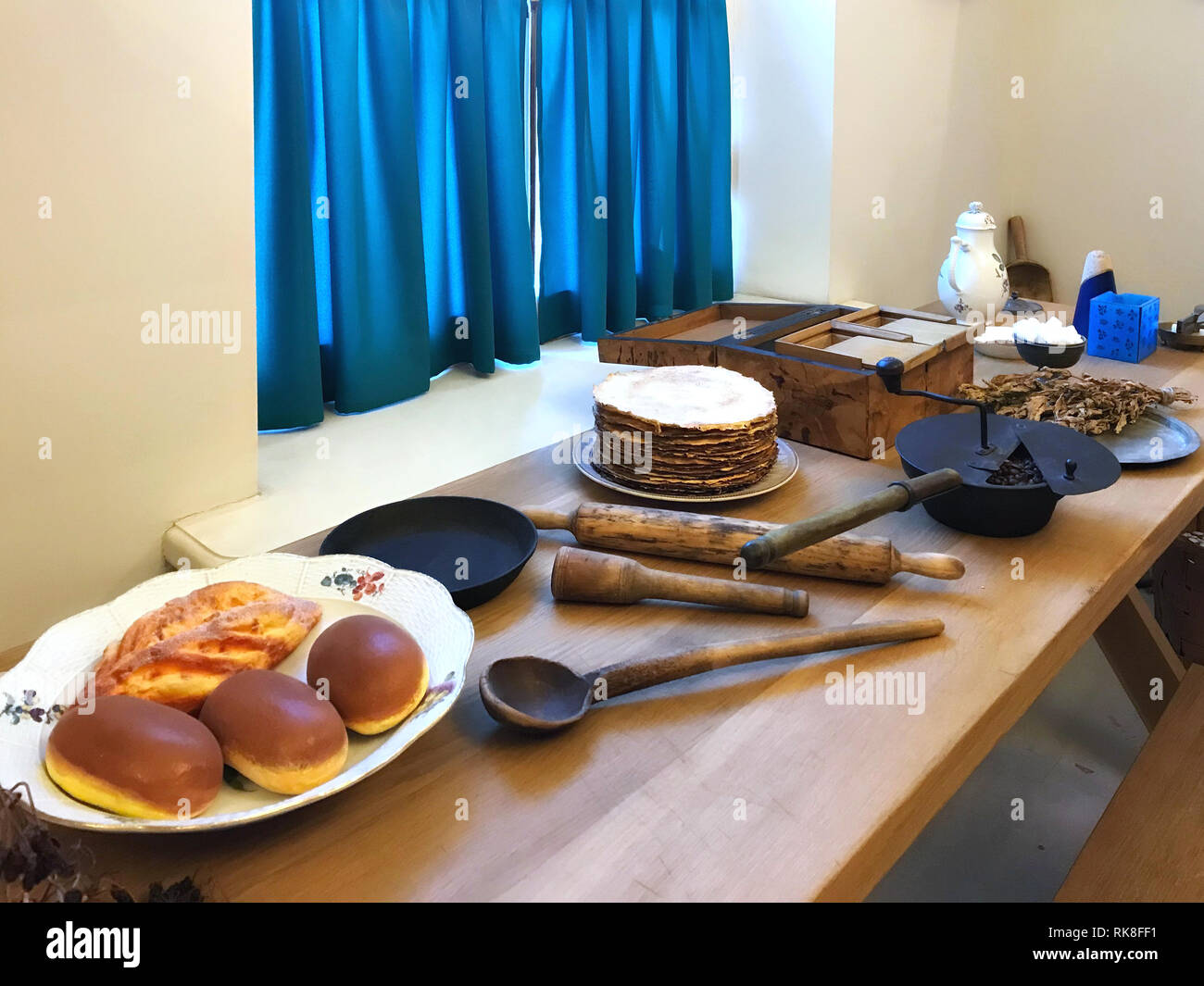 Kitchen interior with a fragment of a dinner table served by food and kitchen utensils. Stock Photo