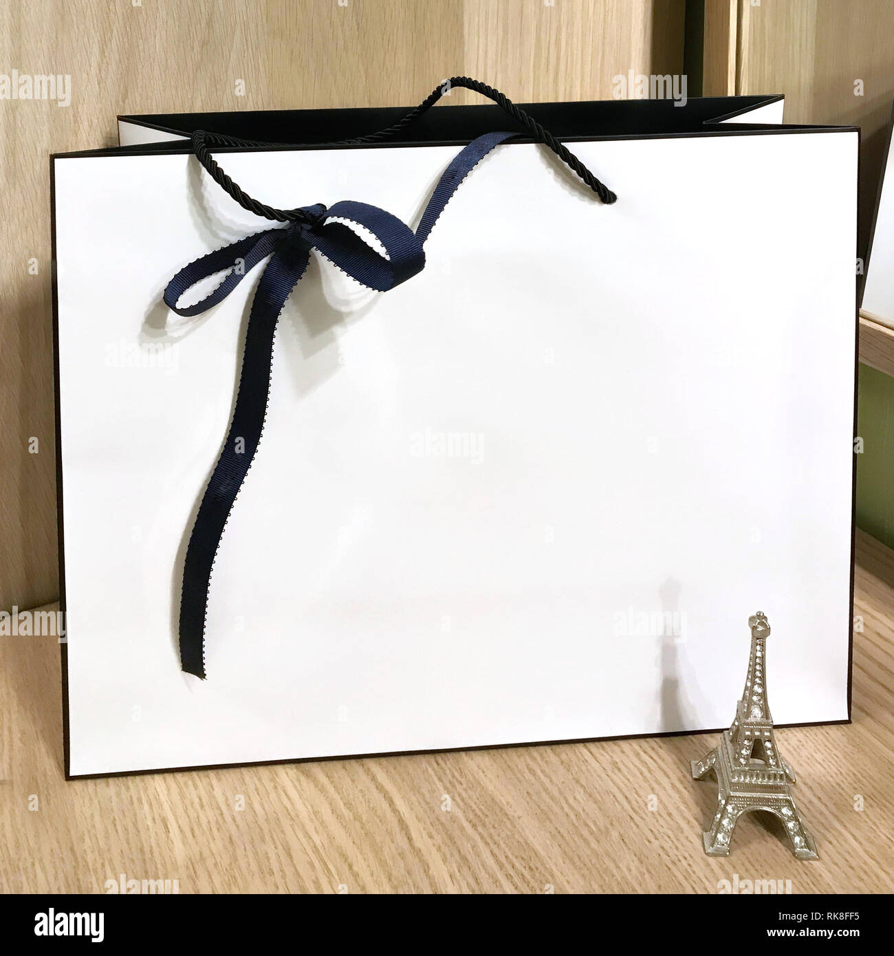 White rectangular bag with handles of black braid and a dark bow. - Stock Image