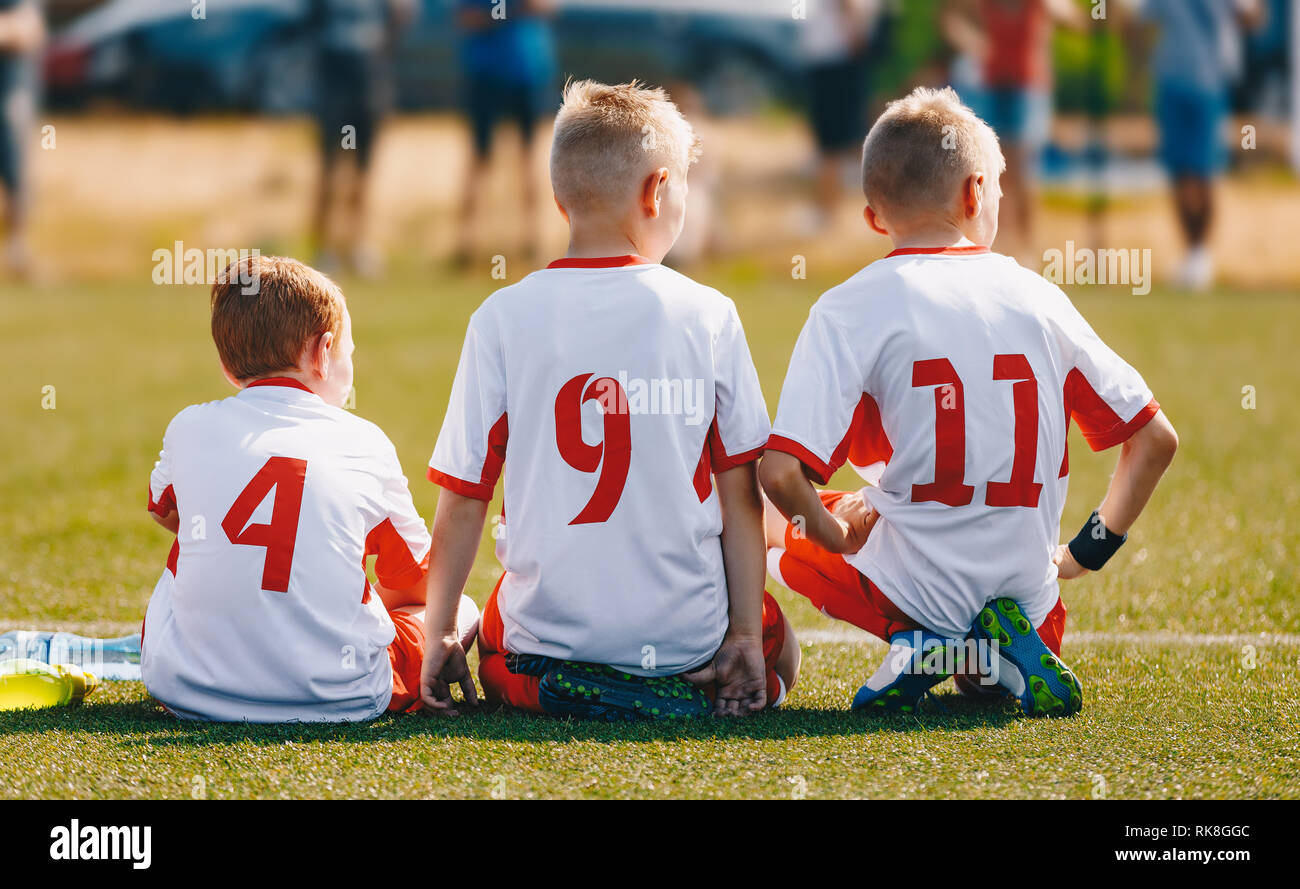 Young Soccer Boys During Football Match. Boys Kicking Football on the Sports Field - Stock Image