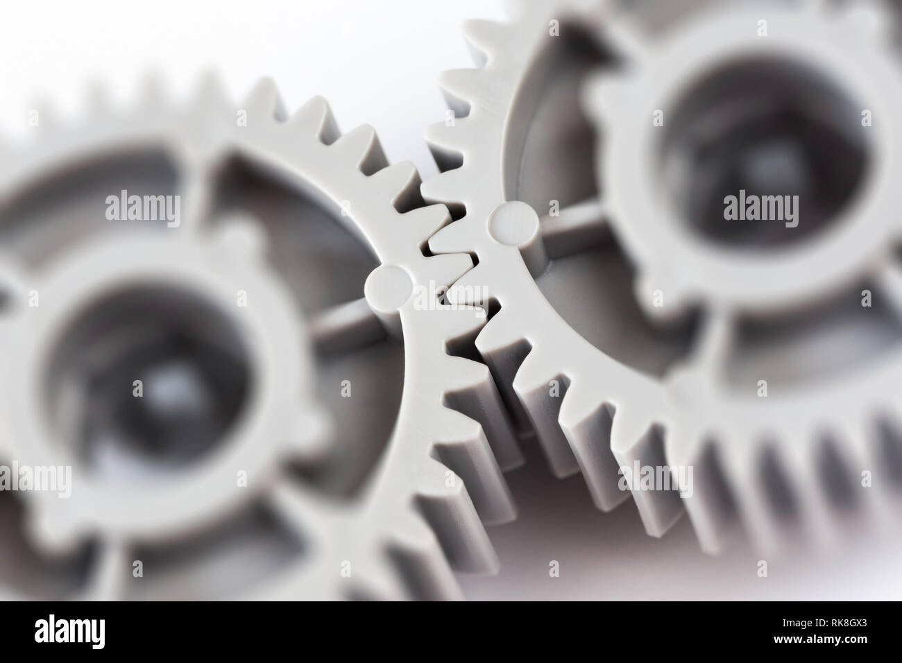 Two gray plastic gears closeup with selective focus - Stock Image