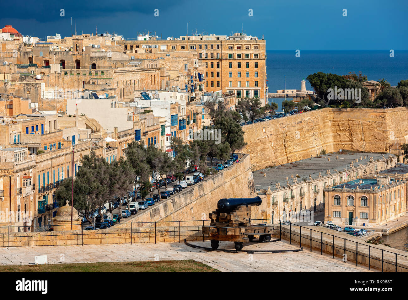 View of old cannon on bastion as city of Valletta on background. - Stock Image