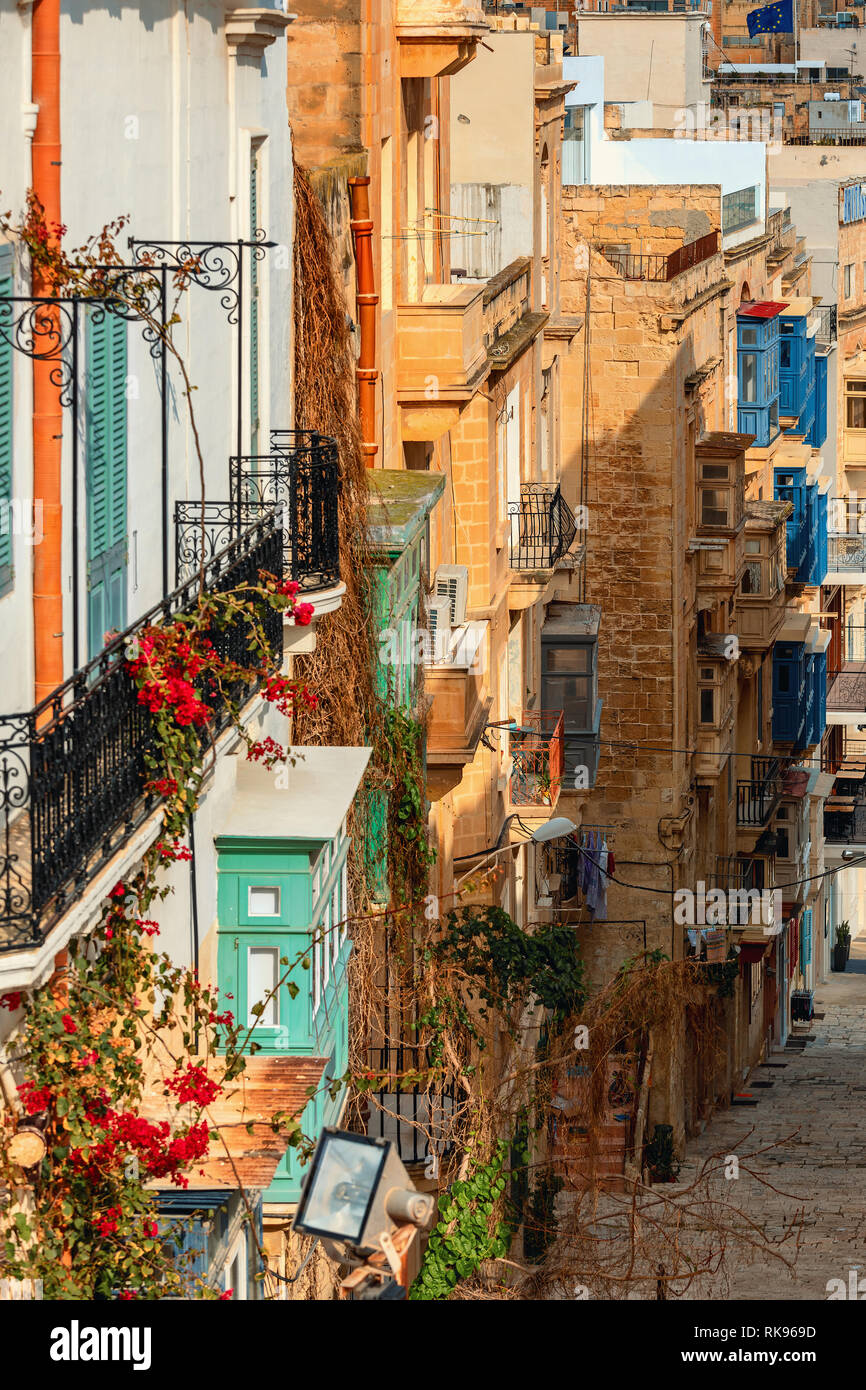 Vertical oriented image of typical stone buildings with colorful balconies along narrow street in Valletta, Malta. - Stock Image