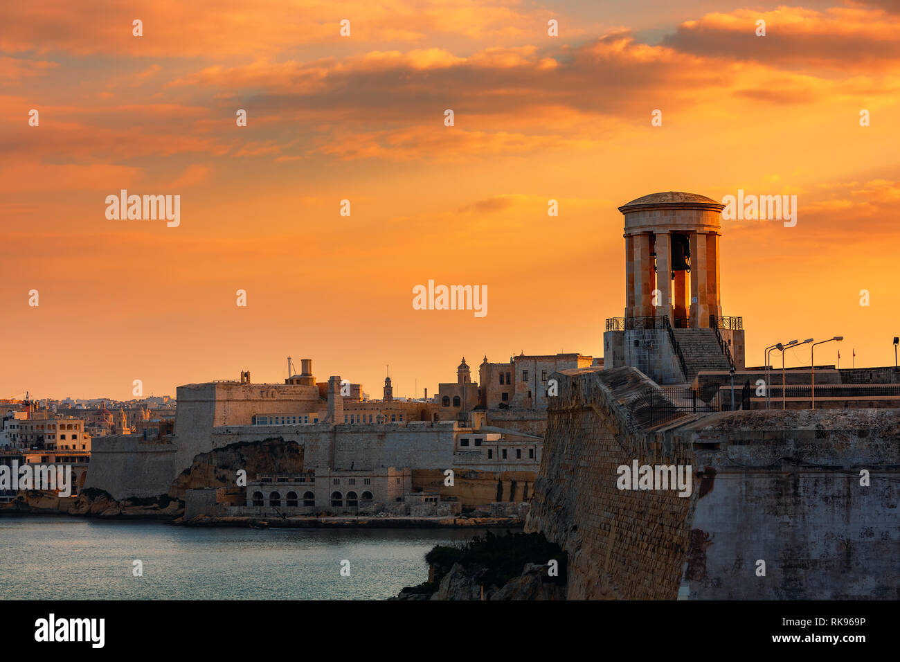 View of Siege Bell War Memorial as old walls and fortress on background under beautiful evening sky in Valletta, Malta. - Stock Image
