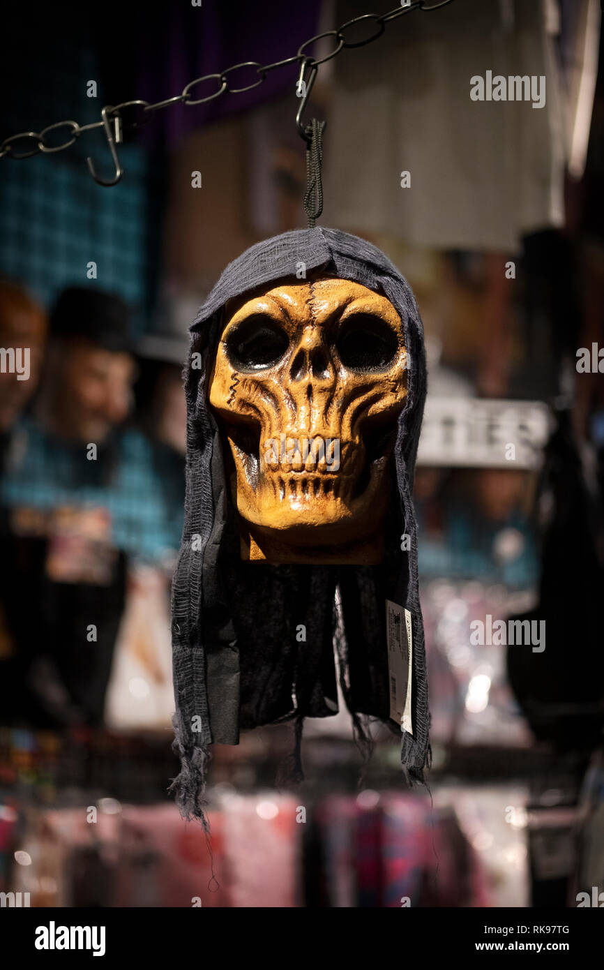 A frightening skeleton's mask in a shroud for sale at the Halloween Adventure, a costume shop in Greenwich Village, Manhattan, New York City. - Stock Image