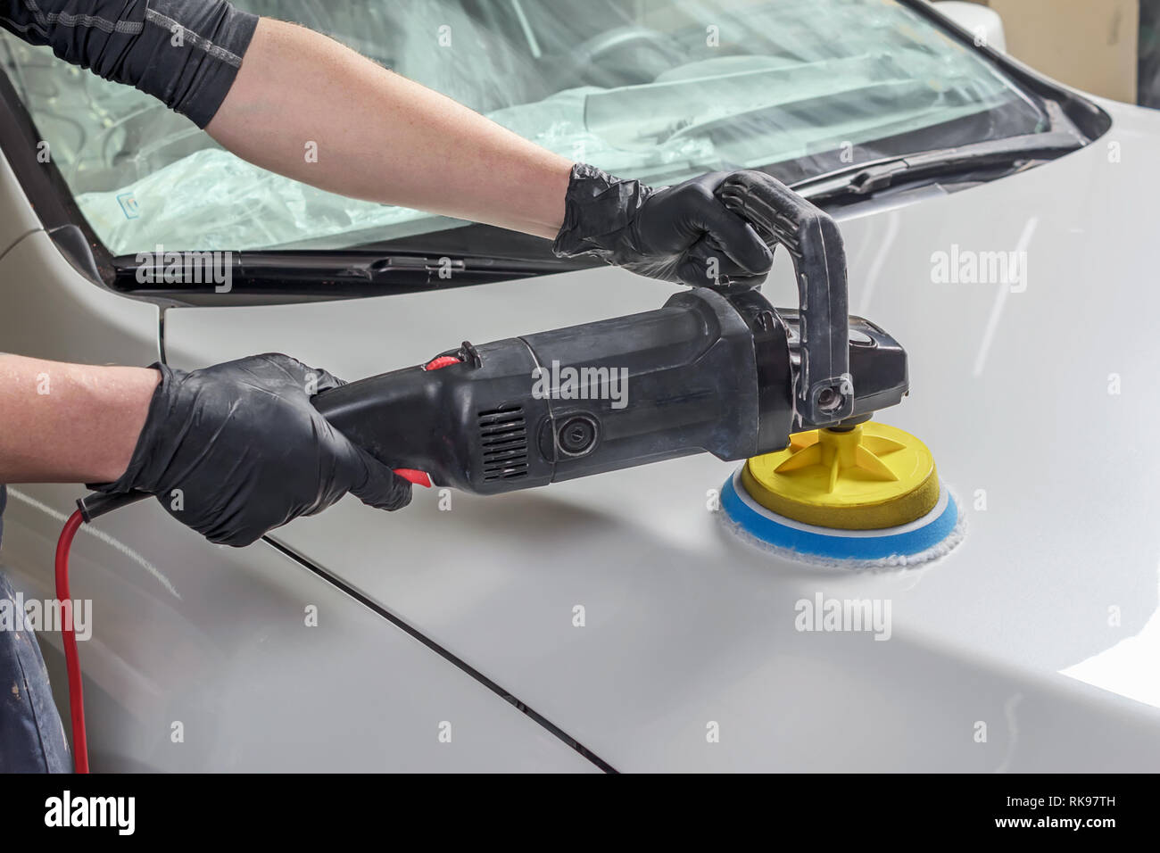 Man holds a polisher in the hand and polishes the car Stock Photo