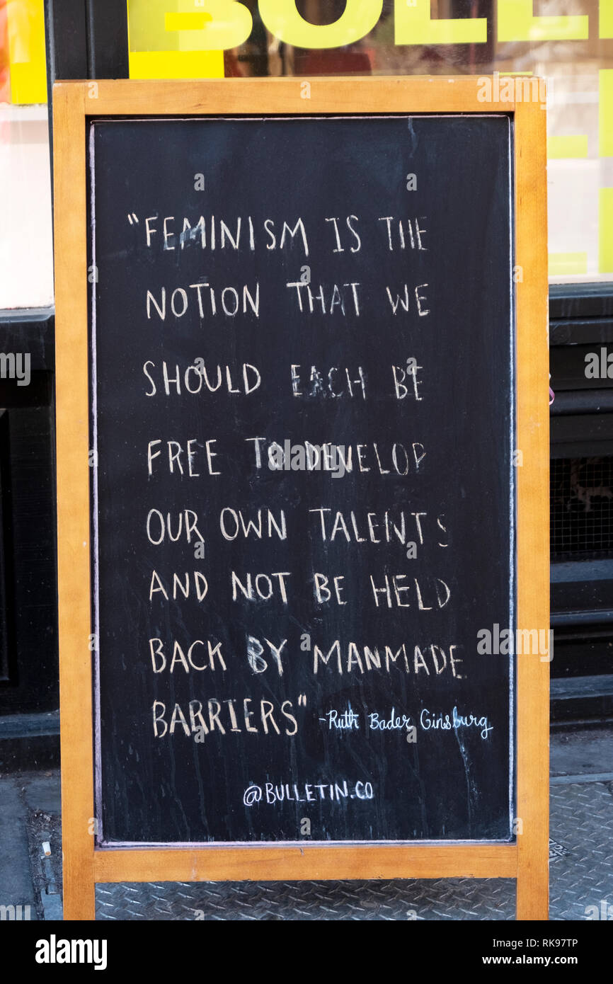 A Ruth Bader Ginsburg quote about feminism on a sign outside the women's clothing store Bulletin on Broadway in lower Manhattan, New York City. - Stock Image