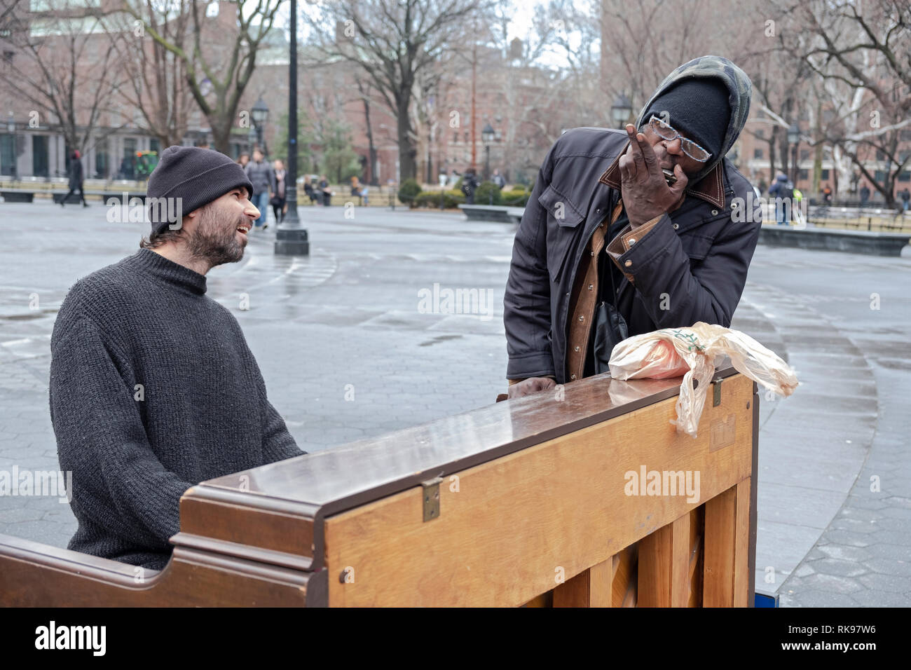 A piano playing busker performs with a passer bye who did blues duets with him on his harmonica. In Washington Square Park in Manhattan, NYC. - Stock Image