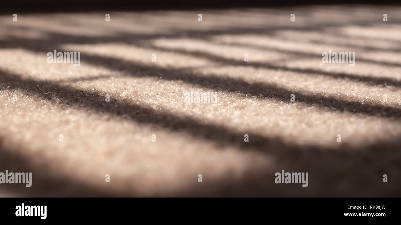 Sunlight filtering through blinds in a window creating a light and shadow pattern on a beige carpet. Image with an extremely shallow depth of field. - Stock Image