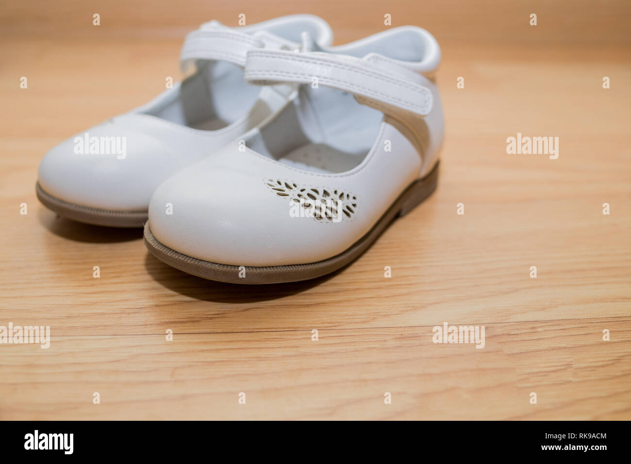 63d4a4d0426a5 Color female shoes. Kids footwear isolated on wooden background.white  leather baby shoes,