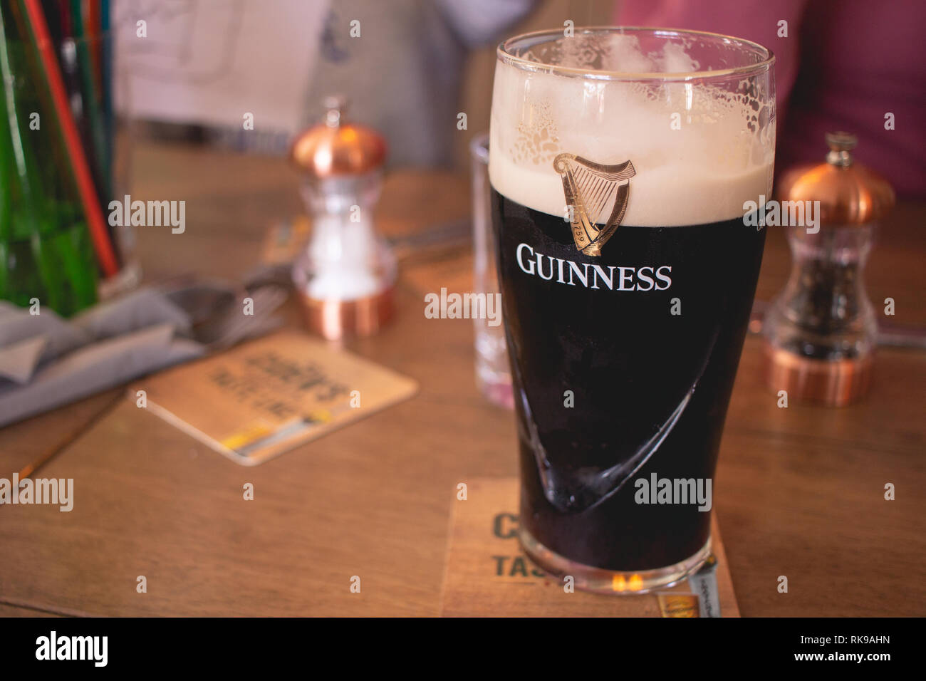 Pint of Guinness on a pub table - Stock Image