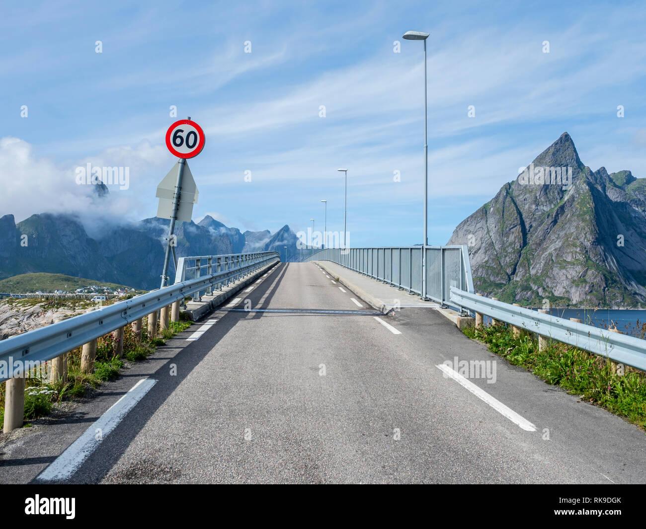 Bridge over Breisundet, at Hamnöy, steep mountan cliff of Olstinden in the back, island Moskenesoy, Lofoten, Norway Stock Photo