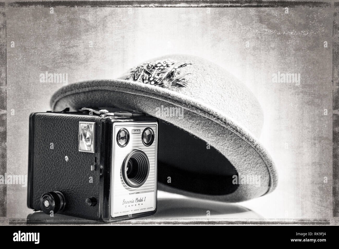 Black & white close up of 1950's Fedora hat leaning artistically on vintage Kodak Box Brownie camera (Model 1) of same period. Aged effect background. - Stock Image