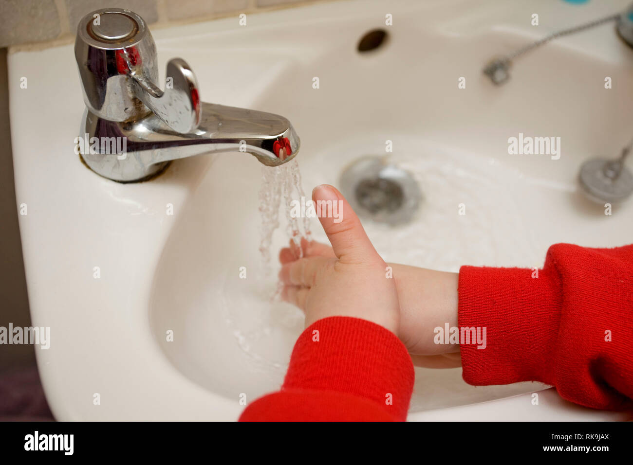 washing hands under hot tap - Stock Image