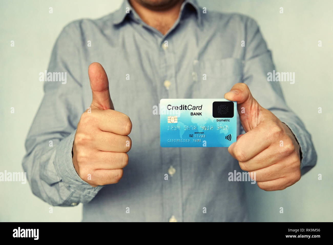 Cropped shot of young man in shirt holding credit card with biometric technology and showing thumb up. Man is glad to use bank card of new type. Advan - Stock Image