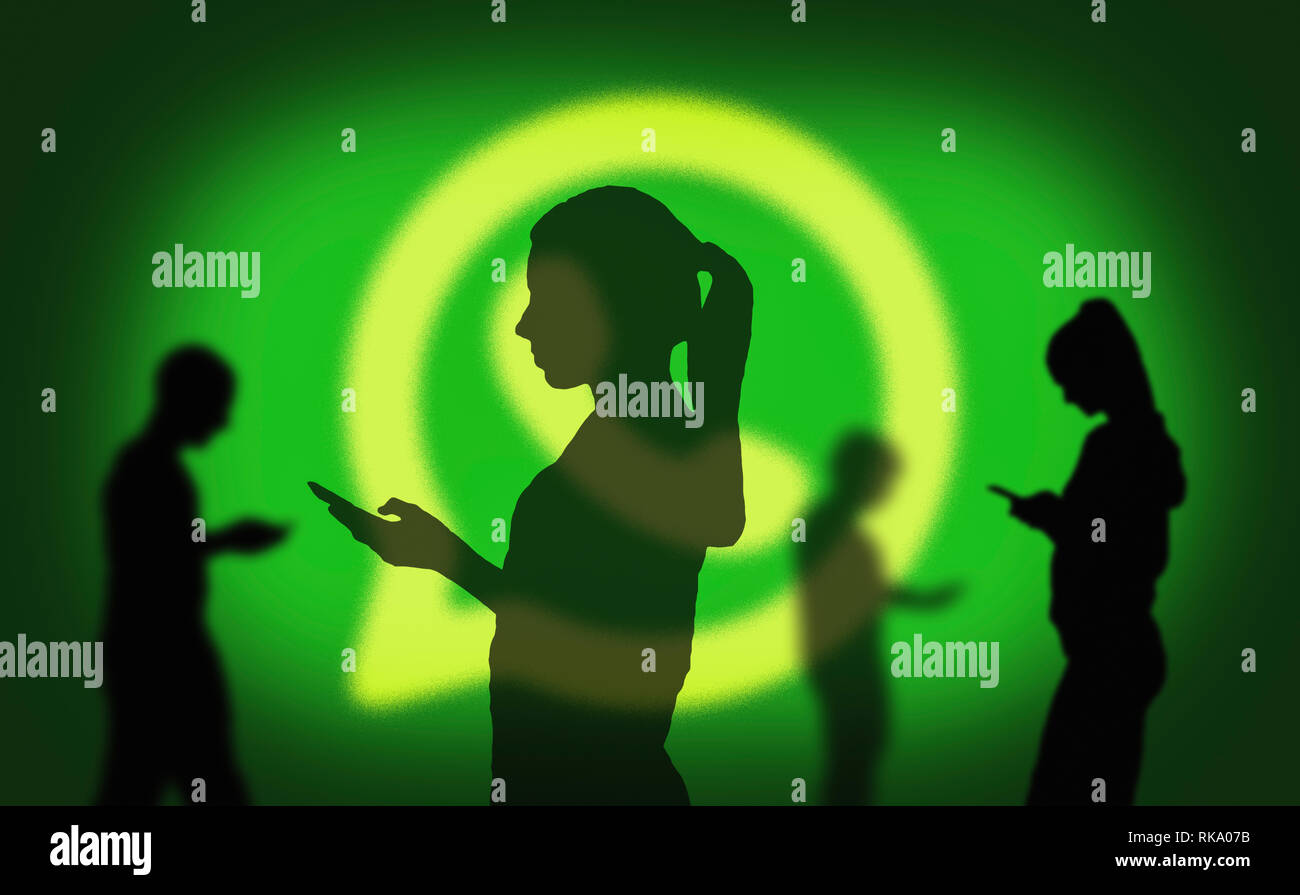 Silhouettes of several people using the WhatsApp app on smartphones for communicating online via the Internet. - Stock Image