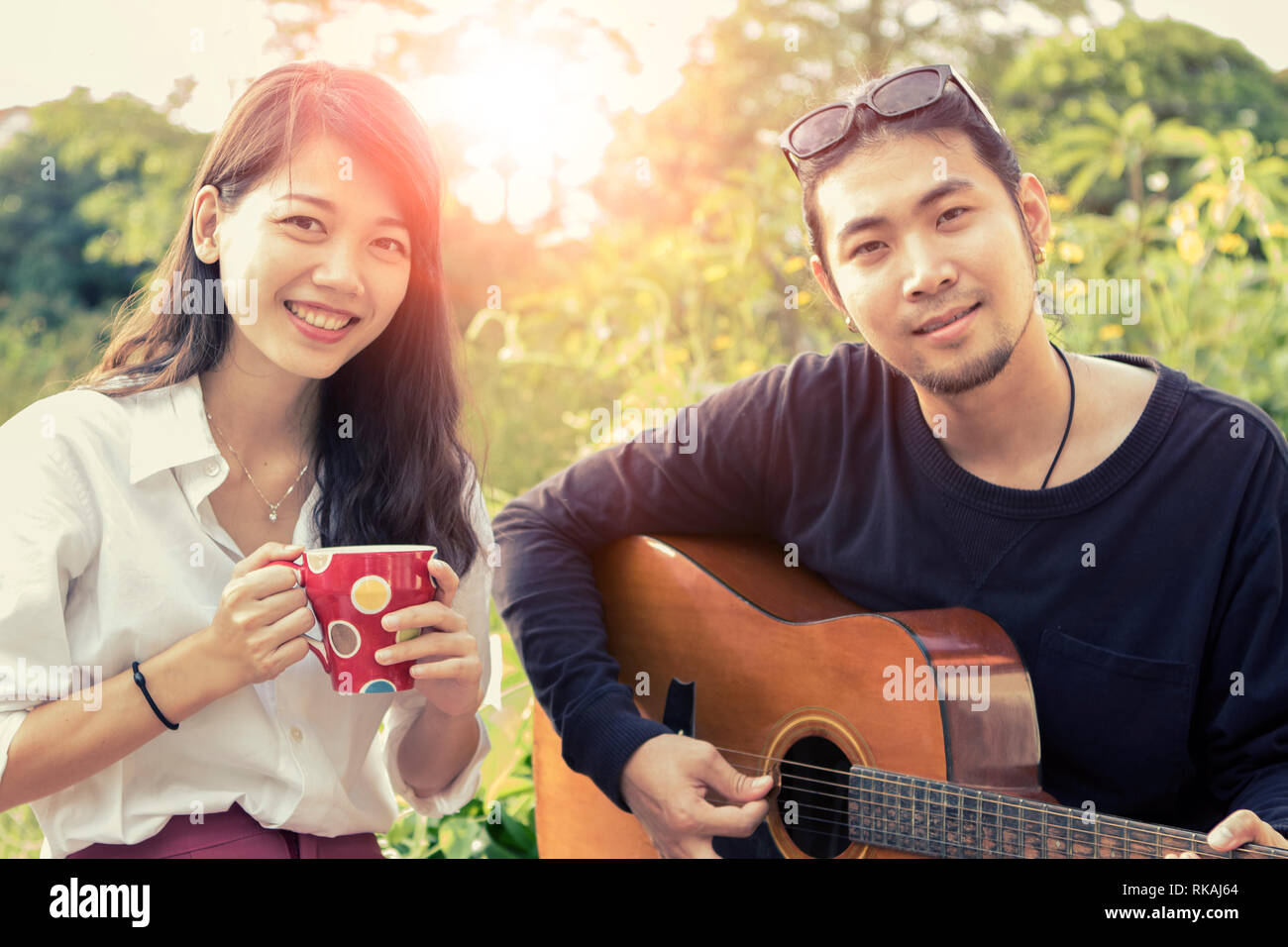 asian younger man and woman playing guitar with happiness emotion - Stock Image