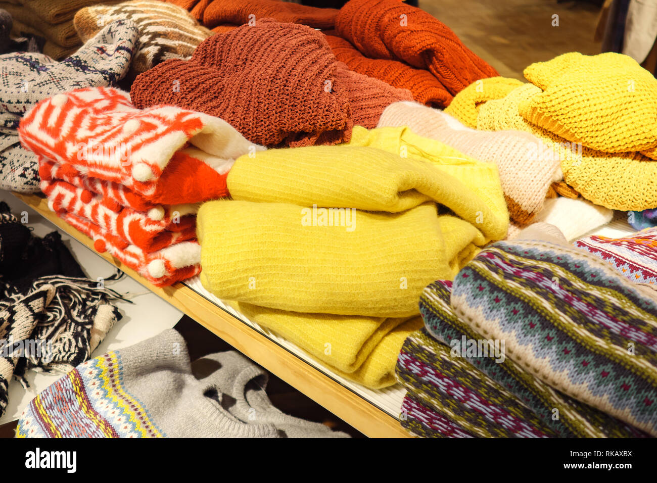 Piles of colorful sweaters on shelf - Stock Image