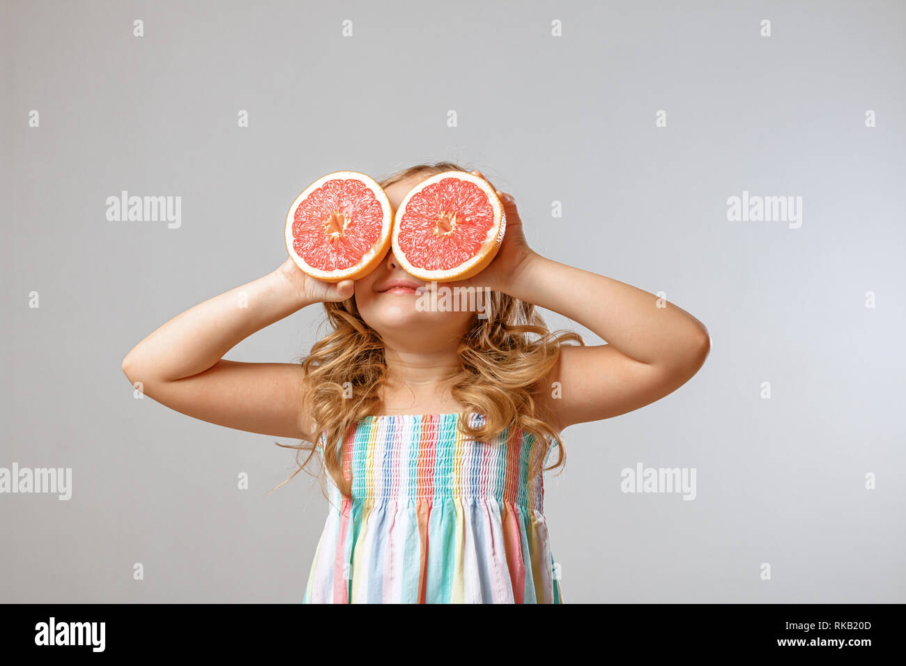 Cheerful little girl child is having fun and substitutes halves of grapefruit instead of eyes. Gray background, studio Stock Photo