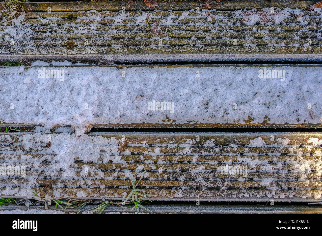 Three wooden decking planks covered with light snow and frost. - Stock Image