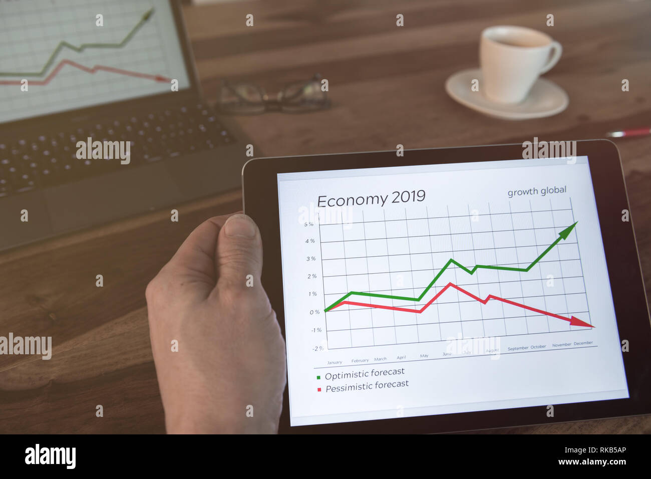 Man is sitting at the table with a tablet in his hand. Economic data is displayed. - Stock Image