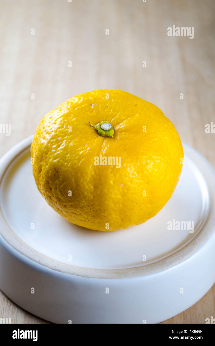 Yuzu fruit (a Japanese citrus variety) on a small white plate against a wooden background - Stock Image