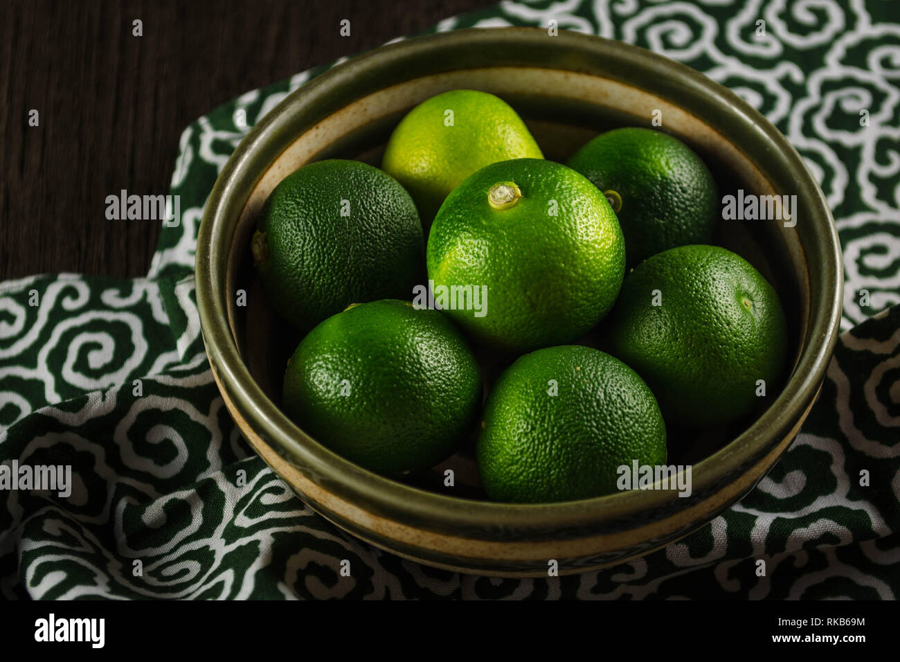 Sudachi - a small, sour citrus used in Japanese cuisine. The fruits go from deep green to bright yellow as they ripen, but remain sour. - Stock Image