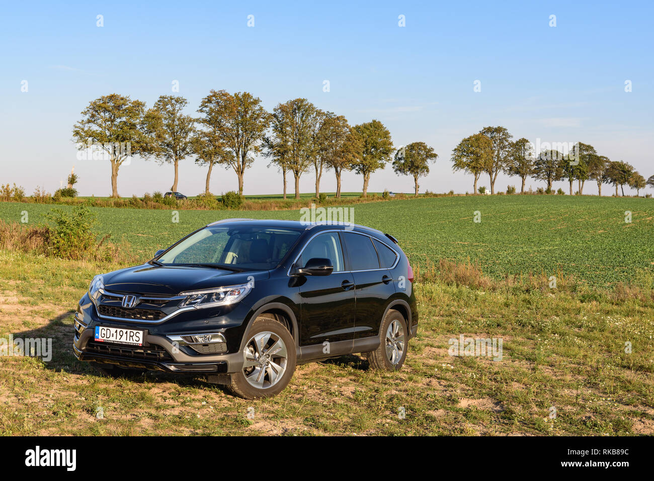 PUCK, POLAND - September 18, 2018: Honda CR-V car parked in a field on a country road next to a wind farm - Stock Image