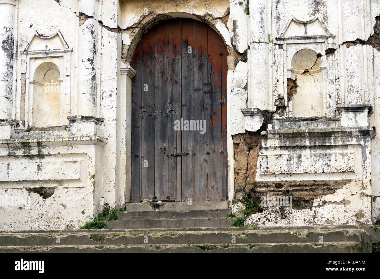 Iglesia en ruinas muy antigua, con puerta al frente desteñida, localizada muy cerca de Antigua Guatemala, ciudad colonial de mucha importancia Stock Photo