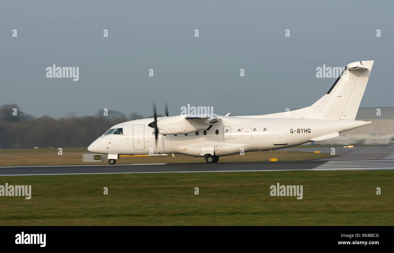 Loganair, Dornier 328-110, G-BYHG at Manchester Airport taxying for take off - Stock Image