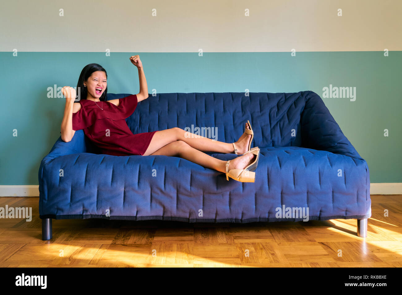 Beautiful woman posing - attractive young woman yelling celebrating victory sitting on sofa - Stock Image