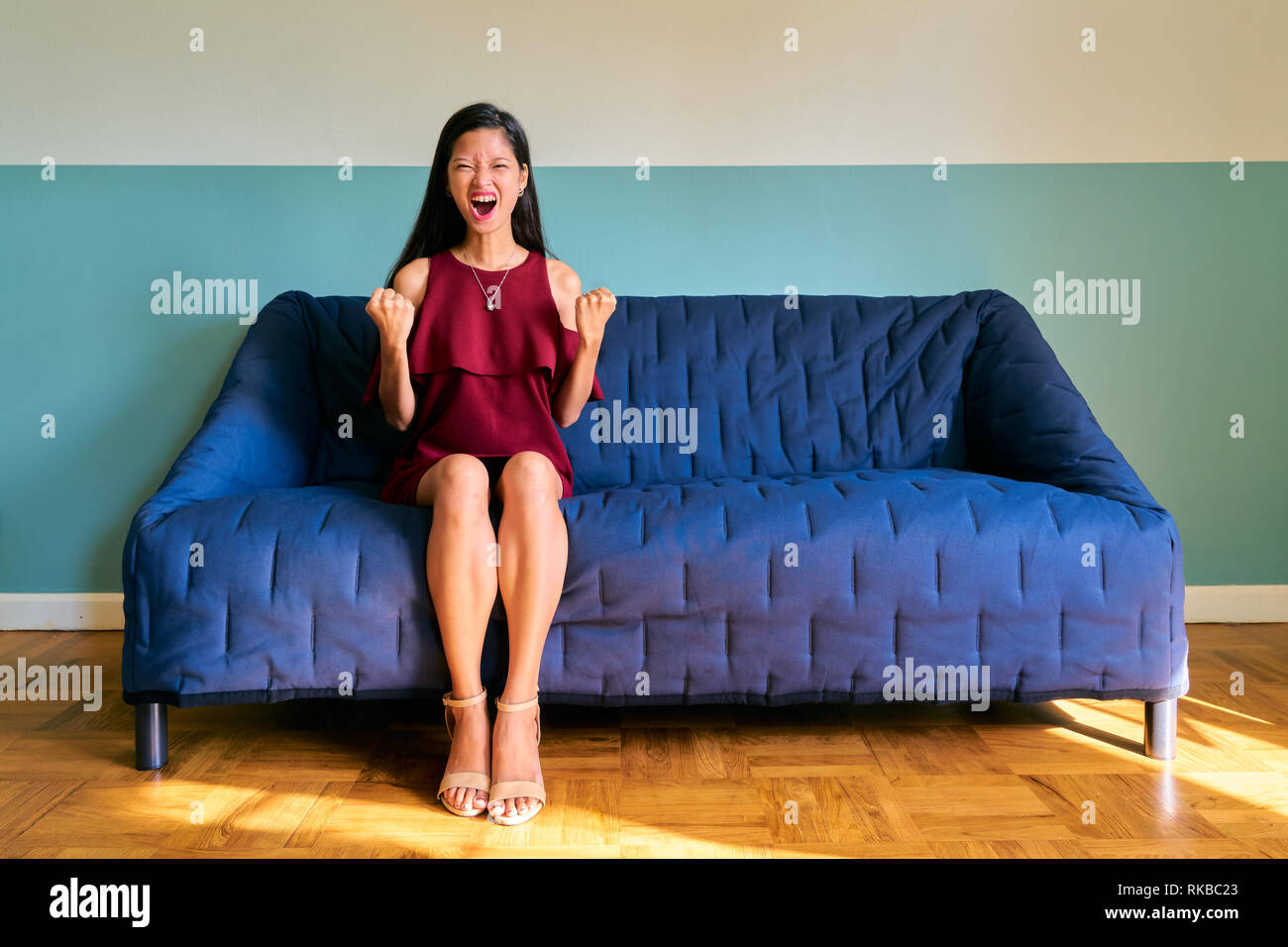 Beautiful woman posing - young woman winning and celebrating sitting on sofa - Stock Image