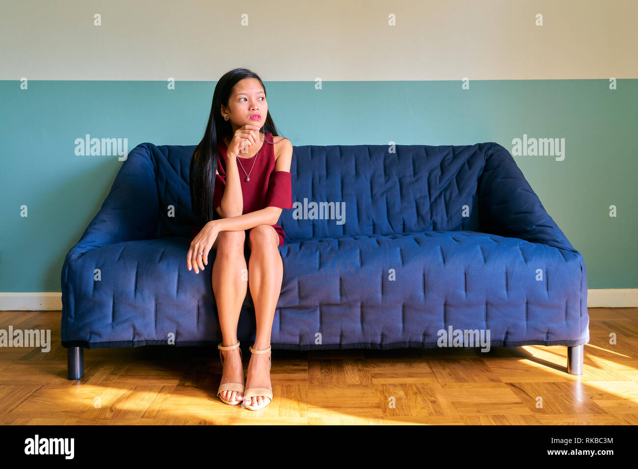 Beautiful woman posing - depressed young woman sitting on sofa - Stock Image