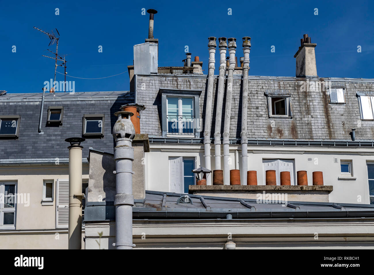 Paris building with attic rooms, tall chimney stacks and grey slate roof tiles  , Paris, France - Stock Image