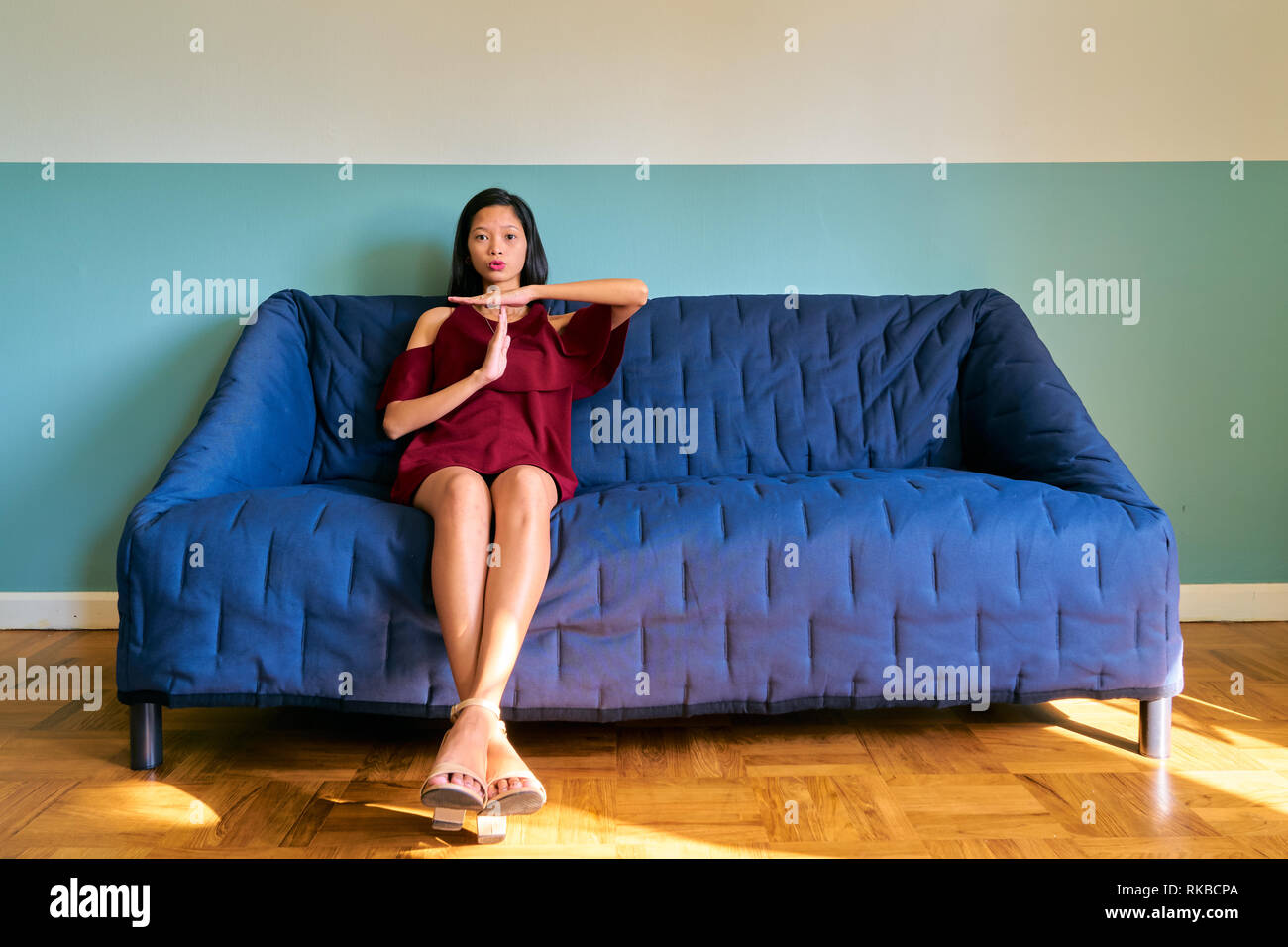 Beautiful woman posing - serious young woman sit on sofa. She shows stop sign with hands. - Stock Image