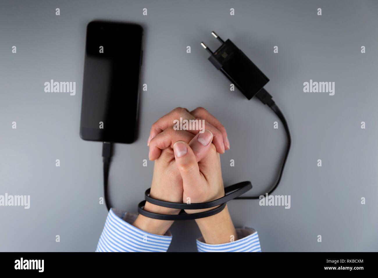 Female hands and smartphone. Woman's hands trapped and wrapped on wrists with mobile phone cable as handcuffs. Addiction to internet and social networ - Stock Image