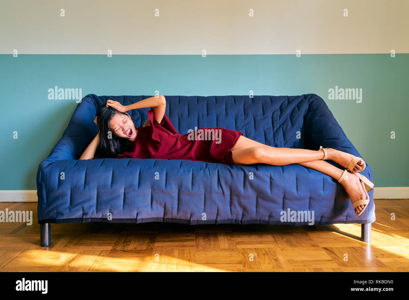 Beautiful woman posing - crazy young woman screaming lying down on the sofa - Stock Image