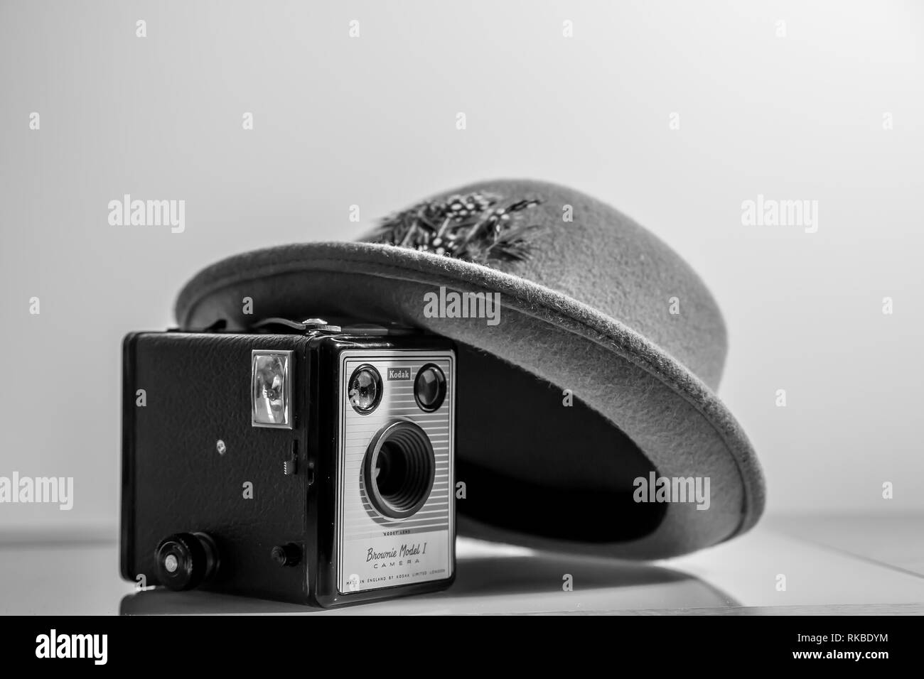 Black and white, interior close up of 1950's Fedora hat leaning artistically on an old, vintage Kodak Box Brownie camera (Model 1) of the same period. - Stock Image
