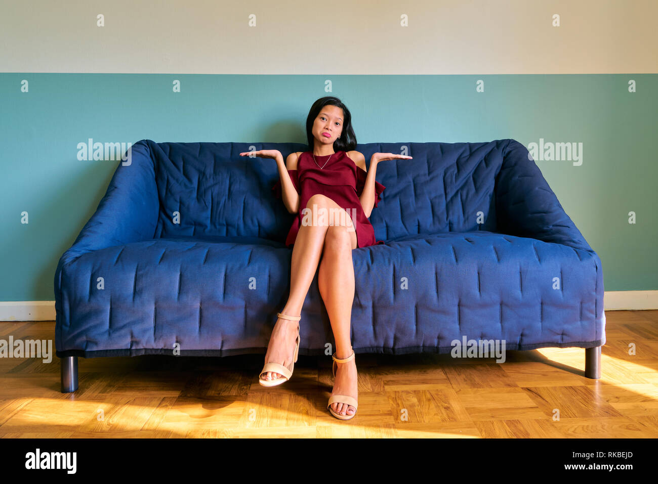 Beautiful woman posing - attractive young woman shrugging sitting on the sofa - Stock Image