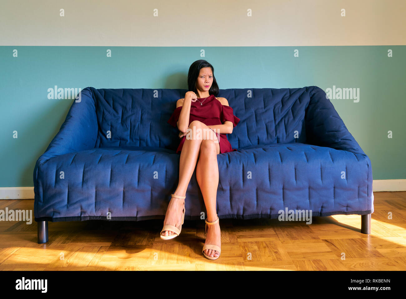 Beautiful woman posing - attractive young woman pointing herself sitting on the sofa - Stock Image